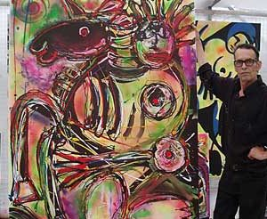 """Jacob Kanbier with his painting """"Unicorn"""" during his exposition in 2015"""